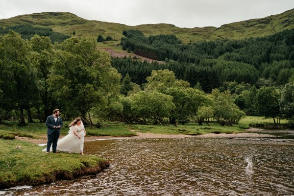 M/F couple dressed in wedding clothes standing by water looking at splash where stone has just landed.