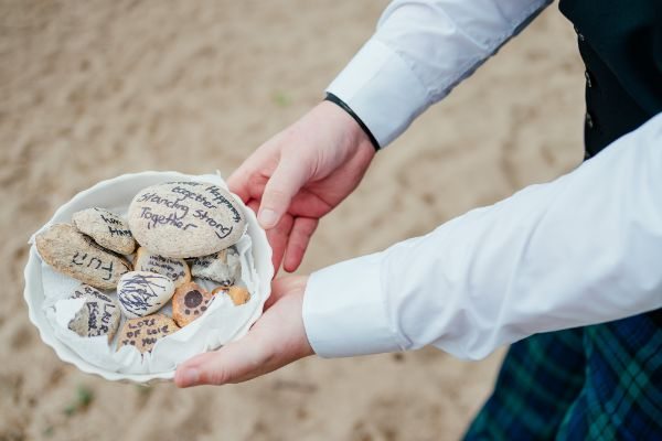 hands holding a bowl containing multiple decorated stones