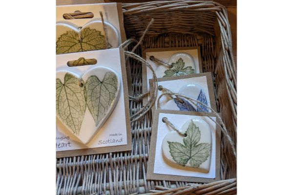Clay hearts decorated with plants in a wicker basket