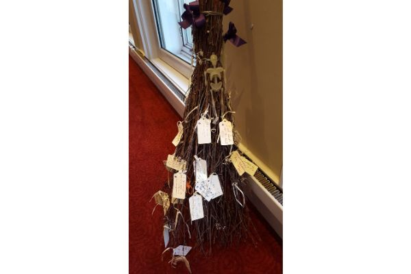 besom broom withpaper labels tied to the twigs