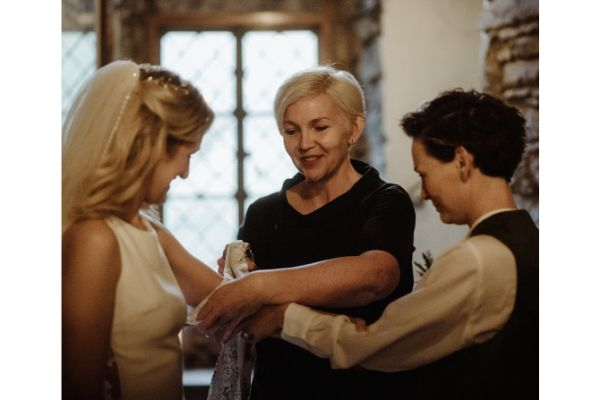 Claire smiling and wrwpping handfasting ribbons round the joined arms of a couple
