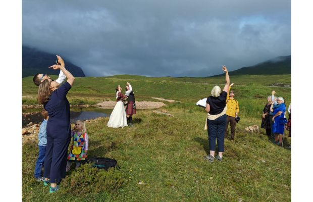 Wedding couple and guests in Glencoe, rudely gesturing to invisible drone flying overheard