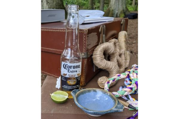 pottery quaich on table next to suitcase, lime and bottle of corona.