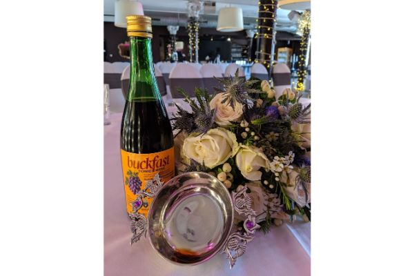 A bottle of Buckfast wine, a quaich and cream toned bouquet on a table