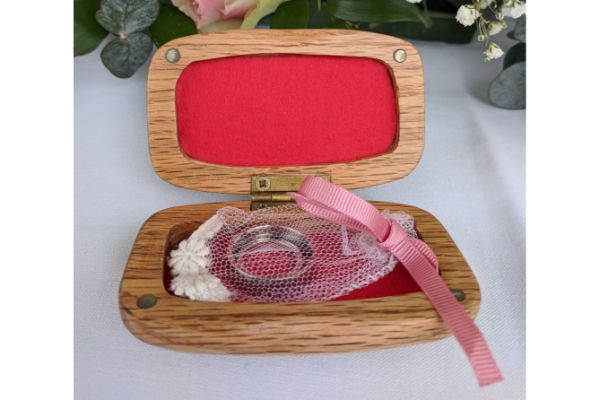 Small wooden box with red lining containing a net bag containing two wedding rings